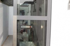 Glass shaft external home lift with stainless steel protection.