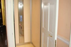 A domestic lift concealed in a cupboard, with door open