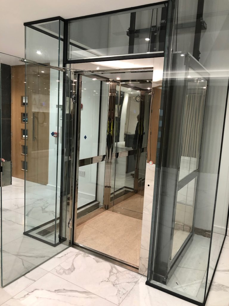 Opened glass door on glass lift at commercial offices in Essex