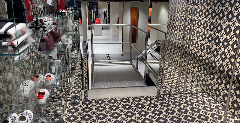 The lift's finish contrasts the upper level with darker tiles seen on the ground floor