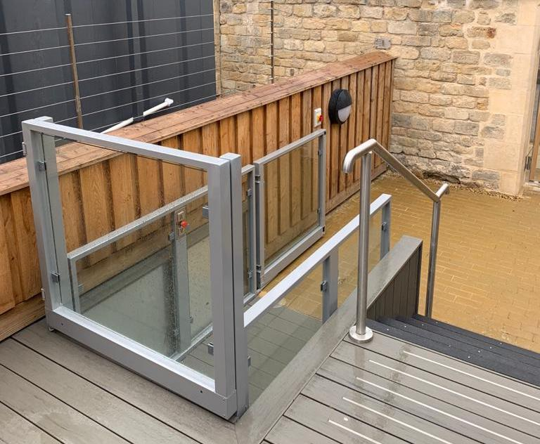 The outdoor lift features the same decking as the upper level and adjacent stairwell