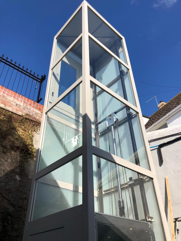 This outdoor home lift in Brixham features a glass and steel self-supporting structure