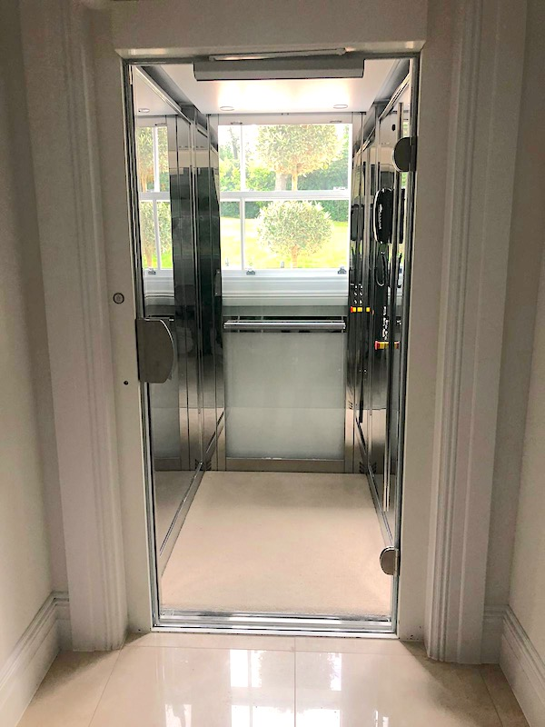 Glass home lift with polished stainless steel cabin