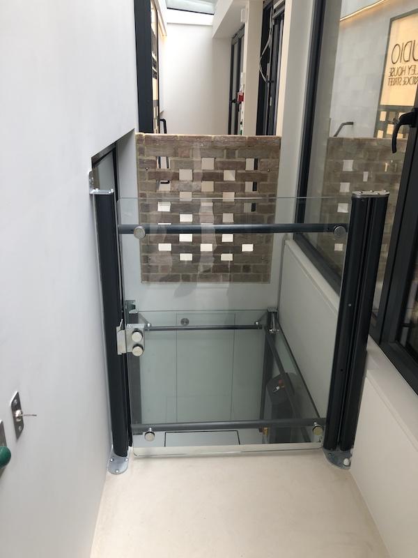 The upper landing features a half height frameless glass door