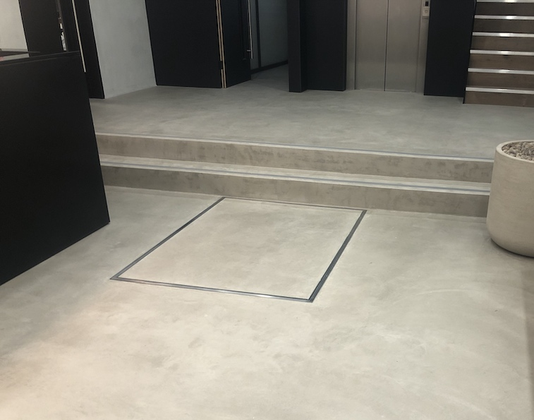 The hidden lift is finished with the same concrete resin as the surrounding floor